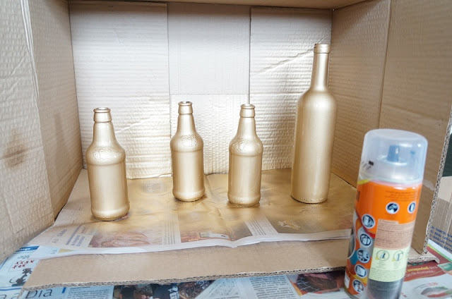 garrafas pintadas de dourado antes da secagem