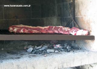 la tira de asado se comienza a cocinar con los huesos hacia abajo