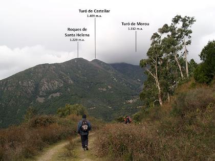 Vistes de les Roques de Santa Helena i del Turó del Castellar, i enmig de la boira el Turó de Morou, des de la Pedrera de la Meca