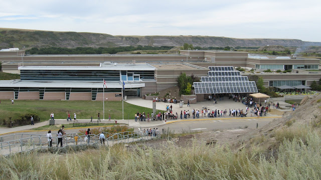 The outside of the Royal Tyrrell Museum, seen from a viewpoint on the museum grounds.  You can see the long line of people stretching out from the front door and into the parking lot.