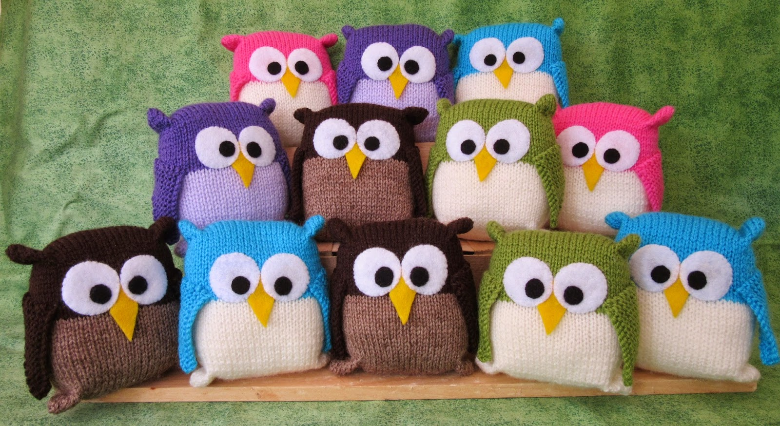 12 knitted owls in various colours sitting in 3 rows