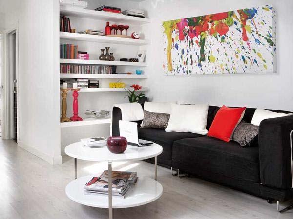 Decoração de sala pequena com sofá de três lugares e mesa de centro redonda.