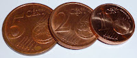 Bild: Auf dem Boden liegt eine 5-Eurocent-Münze, an der Kante darauf eine 2-Eurocent-Münze und an der Kante darauf eine 1-Eurocent-Münze.