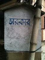 Image of post outside a house with the word 'Sarkar' illustrated in Bengali