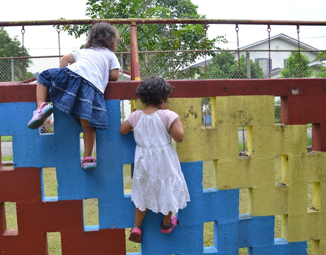 little girls climbing over the wall