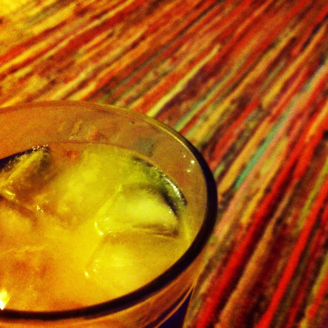 Close up photo of my glass of gin and orange juice. My stripy rug can be seen blurred in the background.