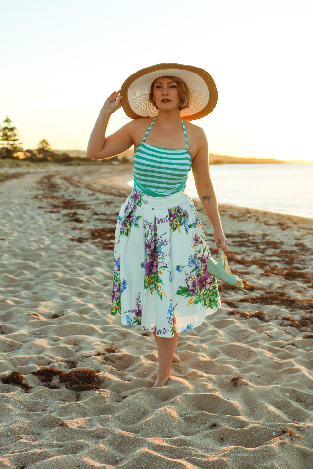 @findingfemme wears mint striped bathing suit and Review Australia floral midi skirt with broad hat at the beach.
