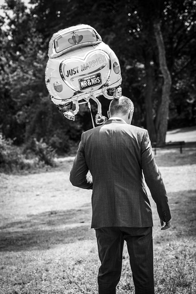 Bräutigam mit Hochzeitsballon im Hofgarten
