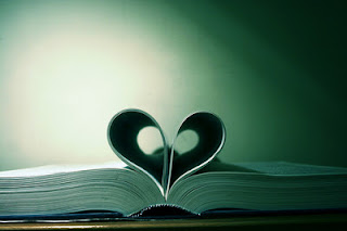 open book with center pages bent to form a heart in the middle