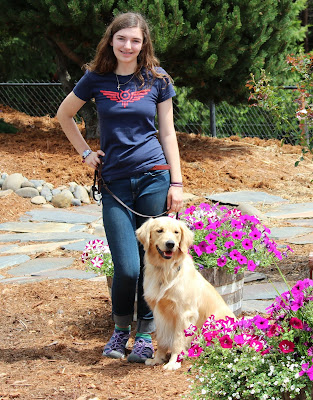 Laura Marchi poses with Golden Retriever Kristoff near purple flower beds.