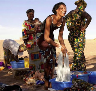 Women wash their clothes at a tap so generously provided by Areva