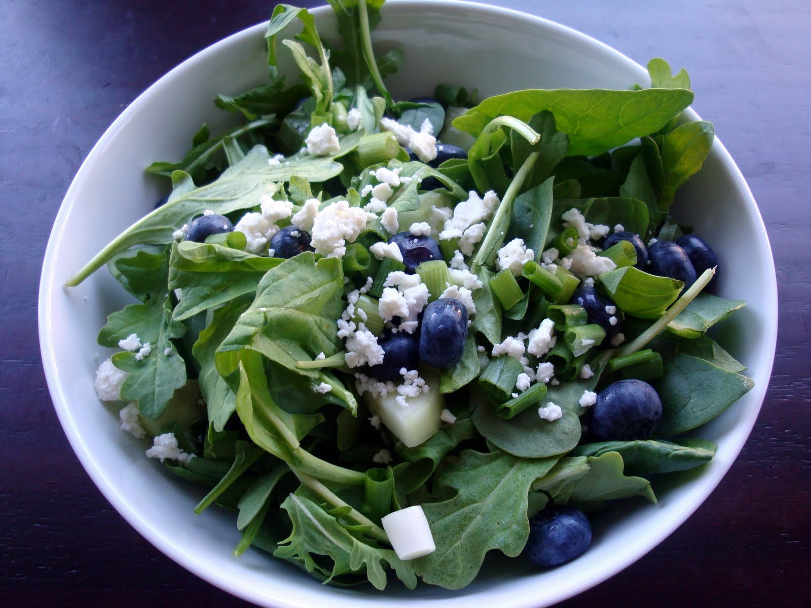 with lots of fresh greens cucumber green onions and blueberries