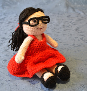 Kwokkie Doll seated and wearing her red sundress, black sandals and black spectacles.