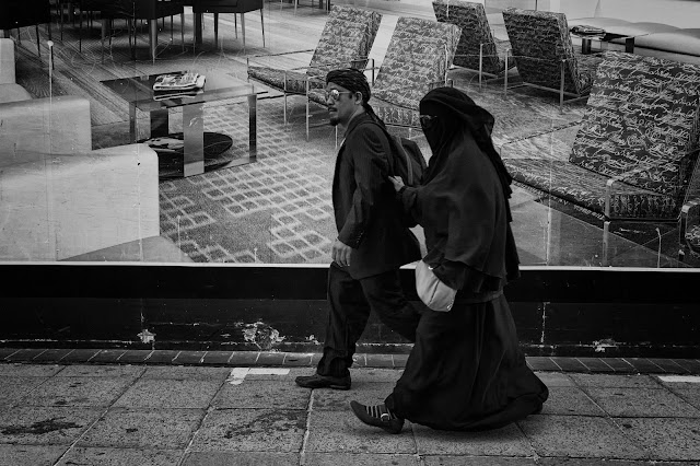 A man and a woman walk past a poster of a living room. She is dressed in a burka and holds his arm