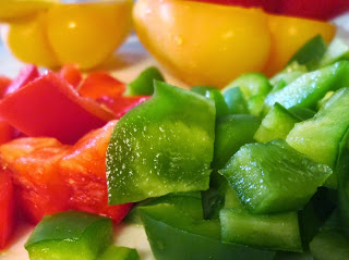 Yellow bell peppers behind small piles of diced red and green bell peppers.