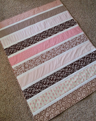 a pink and brown striped baby quilt