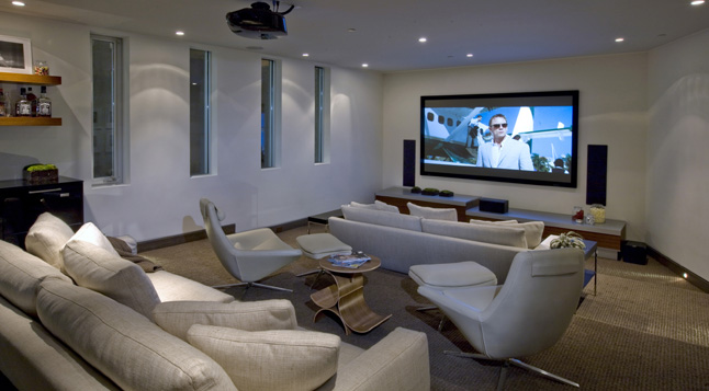 Photo of modern home theater room with lots of sofas and chairs
