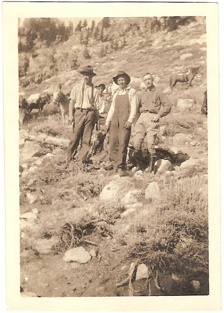 three unidentified men resting from riding their horses on a rocky hillside