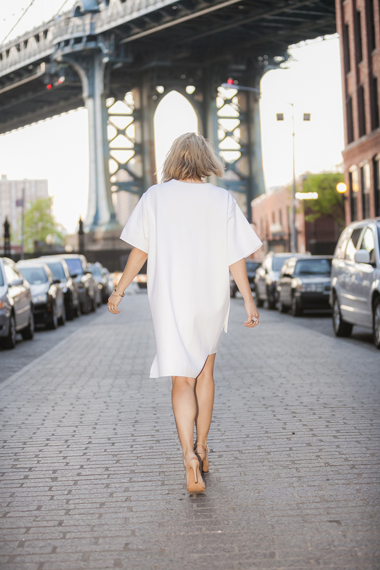 On the street in Brooklyn under the Manhattan Bridge, white dress, gold bangles