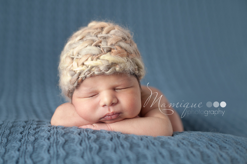 Cute newborn boy sleeping lying on knit blanket