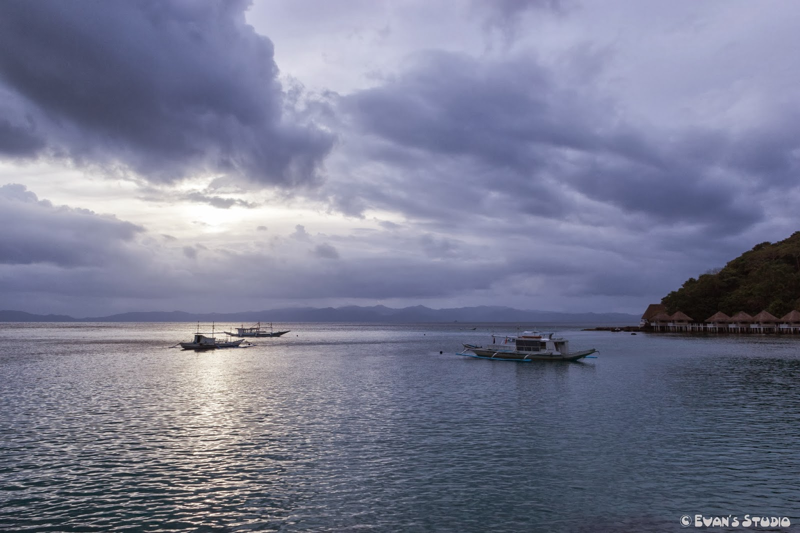 Three ships sit at the outskirts of Apulit Island Resort during dusk.