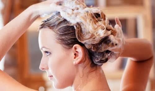 chica lavandose el pelo con jabon