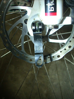 Image showing a Quick release not locked, with the word OPEN visible.  Front disc hub of BTwin Rockrider 5.3 used for demonstration.