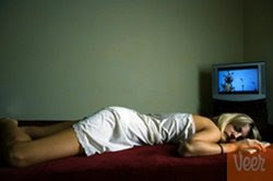Woman asleep in front of TV