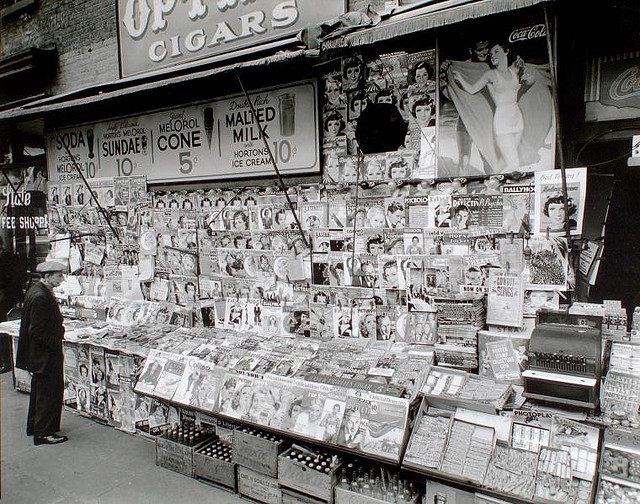 Newsstand, 32nd Street and Third Avenue, Manhattan. November 19, 1935. Notes: Code: III.1.f. Exhibited: Modern Vision #56 Newstand next to State Coffee Shoppe, large display of magazines, ads for sundaes, Coca-Cola above, boxes of sodas below, man at left. Source: Changing New York / Berenice Abbott. Repository: The New York Public Library. Photography Collection, Miriam and Ira D. Wallach Division of Art, Prints and Photographs.