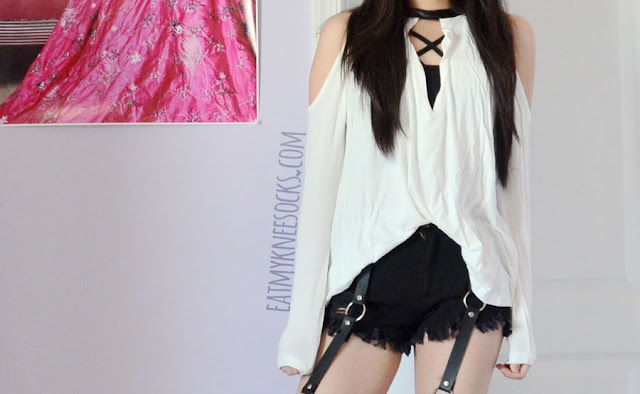 An edgy, grunge-style outfit with the leather-trim cold shoulder SheIn top, a strappy bralette, Harajuku-style frayed harness shorts, and spiked high-heel Jeffrey Campbell Lita dupe booties.