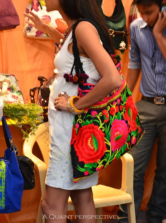 She carries a tote with pom-poms and distinctly Parsi floral embroidery in primary hues of red, blue and yellow.