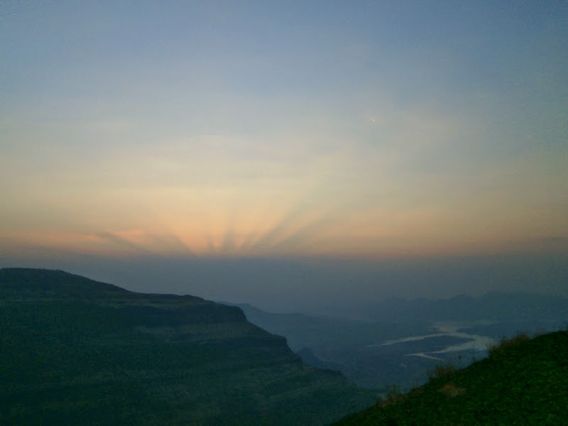The first rays of the sun coming out in the sky between Kalsubai and the Ghatghar Dam