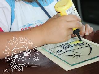 Szöveg: A már megrajzolt és enyhén megszáradt kontúrrajzokat átadtam az illetékesnek, hogy fesse ki. Kép: Közelkép egy másik gyermek kezeiről, amint kicsire vágott üveglapon színezi az előre megrajzolt és megszáradt Törpmanó házikóját.