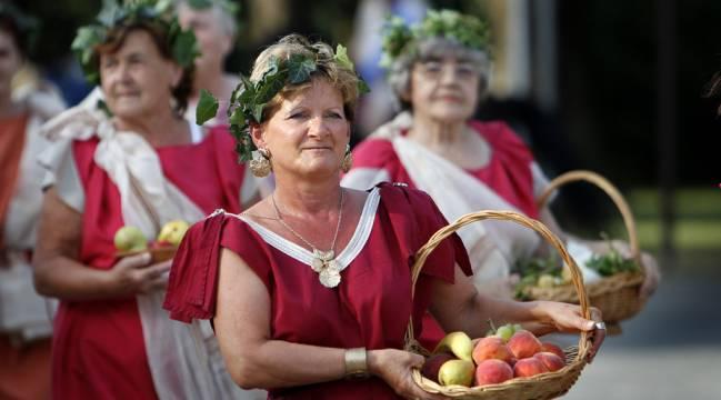 Starije dame u rimskim togama u korpama nose voće