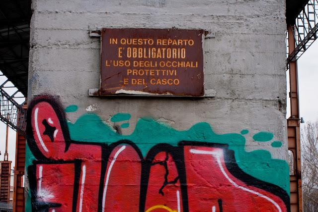 immagine: vecchio cartello di fabbrica e Graffiti in Parco Dora