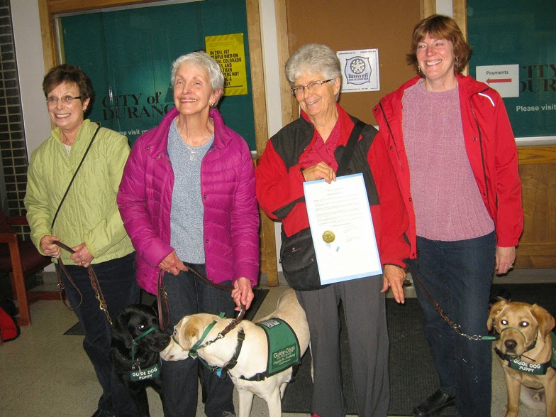 Puppy raisers from the club Southwest Bright Eyes holding up the proclamation certificate, along with their puppies in training.
