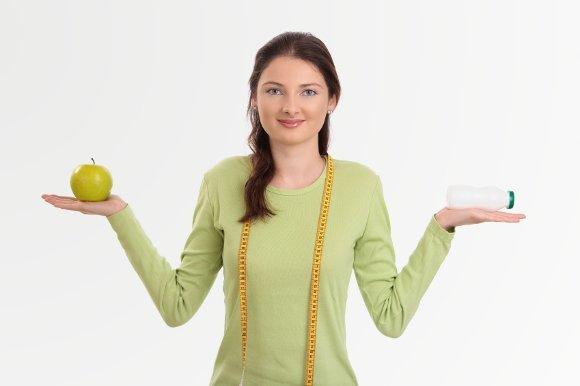 woman holding probiotic and apple