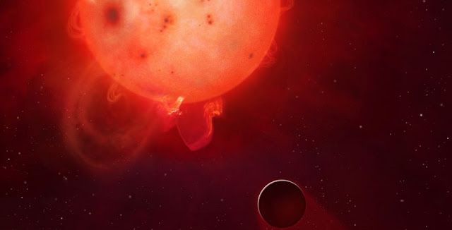 The planet Kepler-438b is shown here in front of its violent parent star. It is regularly irradiated by huge flares of radiation, which could render the planet uninhabitable. Here the planet's atmosphere is shown being stripped away. Image Credit: Mark A Garlick / University of Warwick