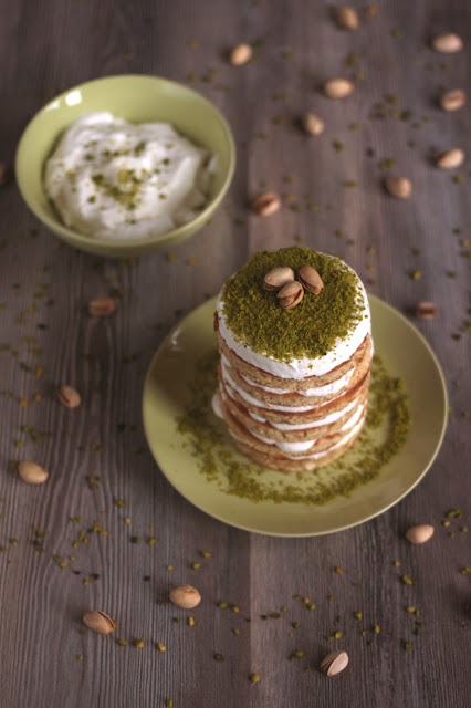 A pancake stack recipe with white chocolate in the batter, ground pistachios on top and a sweet vanilla whip cream. Made by the German food blog Pancake Stories.
