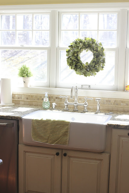 Shaw's farm sink with Graff bridge faucet with wreath on window via www.goldenboysandme.com