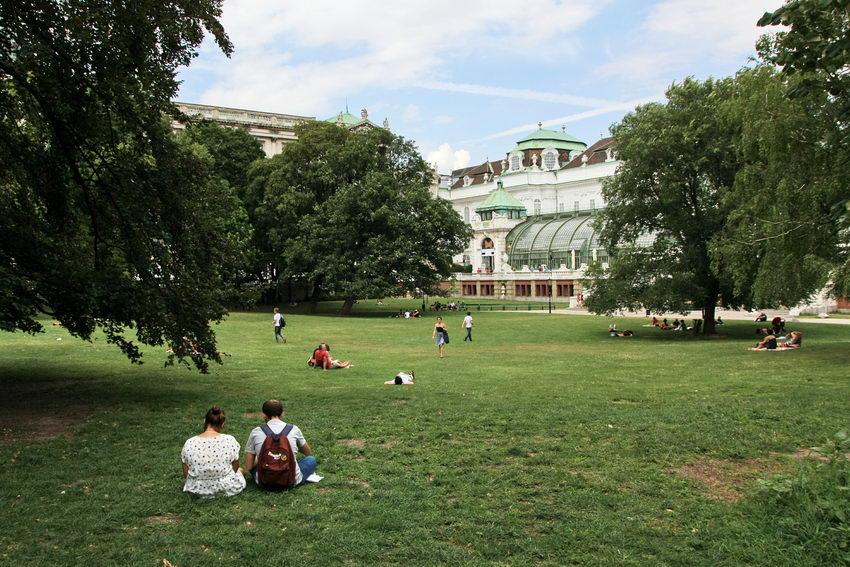 Por menor duma clareira do parque rodeada de árvores de grande porte. E primeiro plano um casa sentado na relva e várias outras pessoas mais ao longe