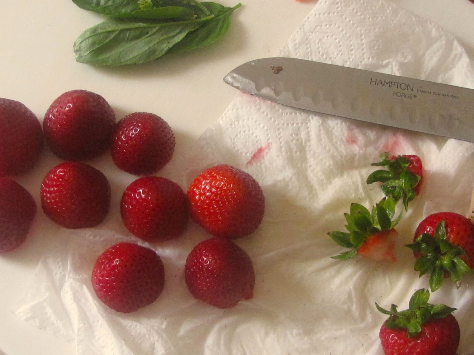 Hulled Strawberries with basil leaves on a white board