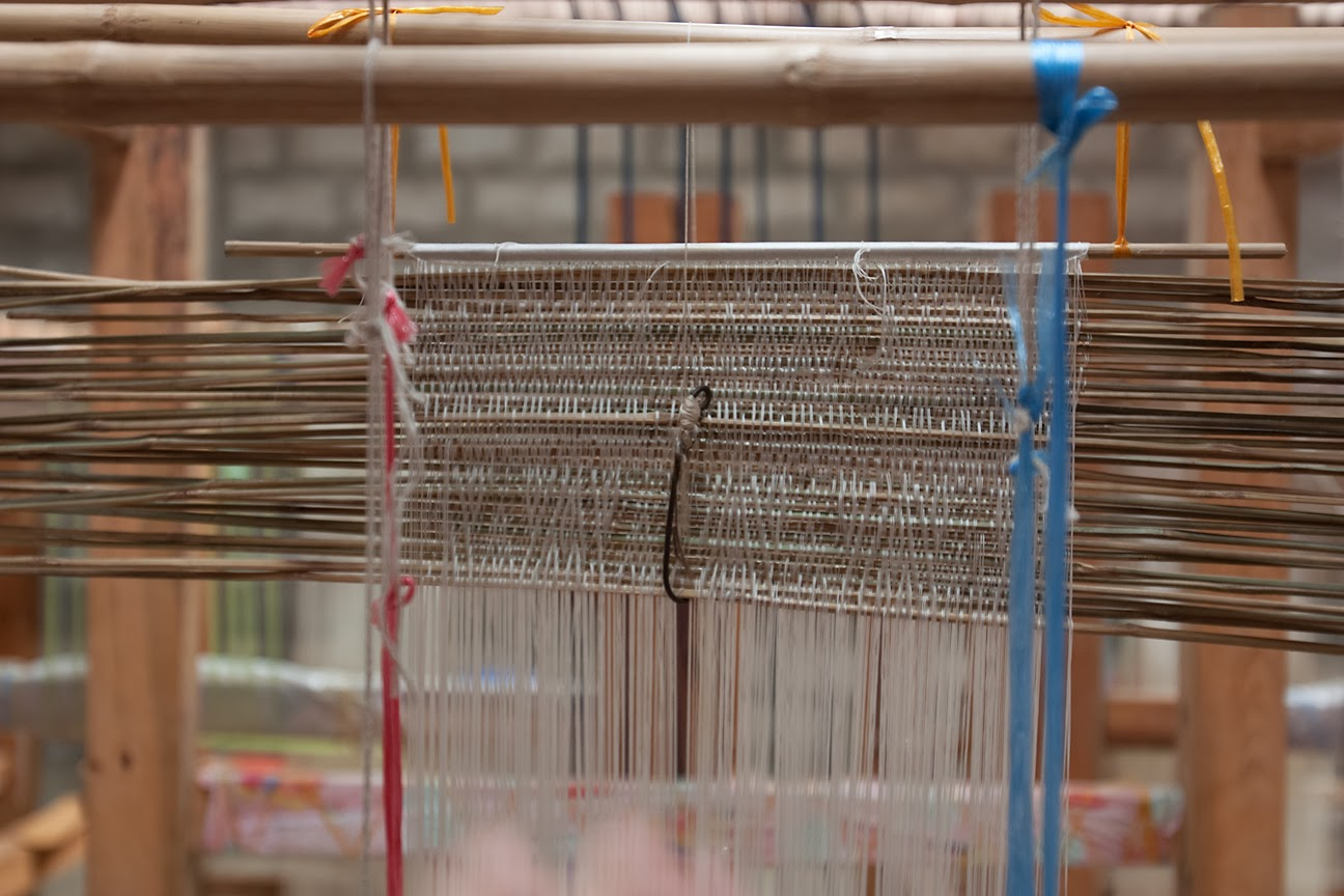 A skillfully tied string heddle on the loom controls a complex design. Strips of bamboo are used to carry the pattern.