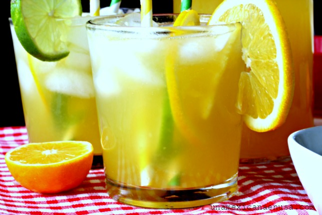 Refresco de mandarina servido en vaso con hielo y rodajas de naranja.