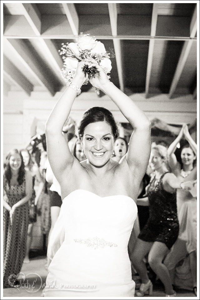 bride has wild guests behind her for the bouquet toss