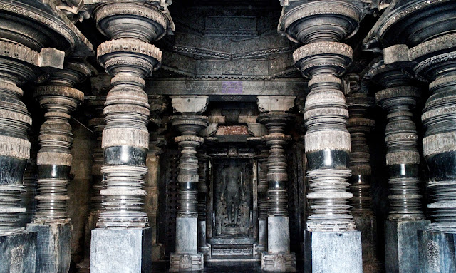 10 of the 12 elegantly carved pillars of the navaranga, Parshvanatha statue at the center, and the ceiling sculptures partially visible through the door.