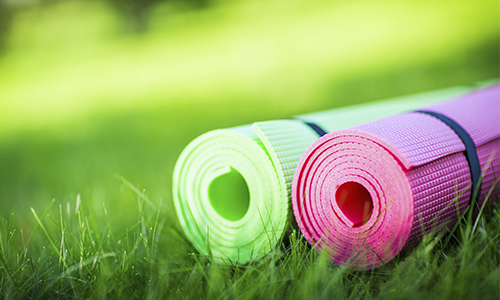 Rolled yoga style mats in the grass.