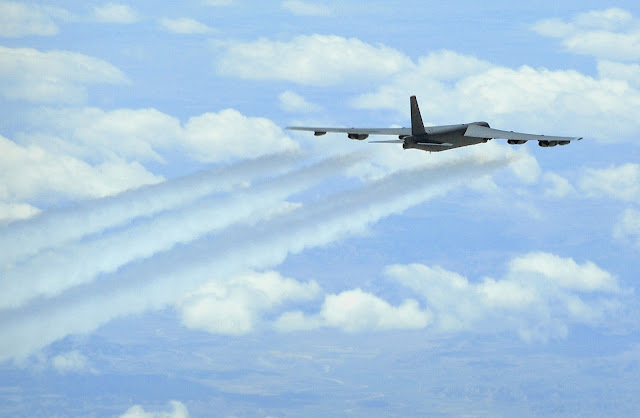 A B-52 Stratofortress flying with contrails.