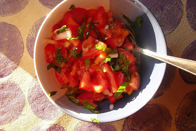Schüssel mit Tomatensalat auf handbedrucktem Tischset