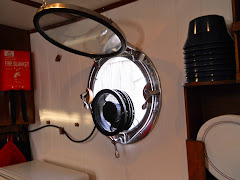 Fred's latest! A new galley porthole exhaust fan! Storage bracket to the left. VERY happy we are!